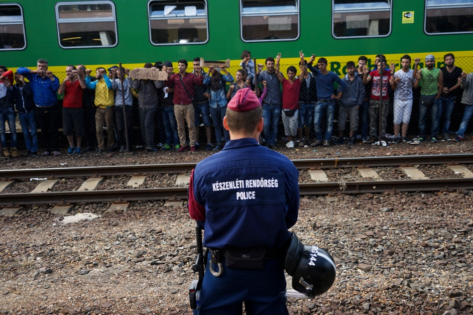A policeman watches as Syrian refugees strike at the platform of Budapest Keleti railway station, Hungary, September 4, 2015. (Mstyslav Chernov-Wikimedia Commons)